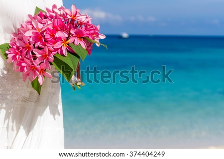 bright tropical flower bouquet in hands of young beautiful bride on blue beach and sea background - stock photo