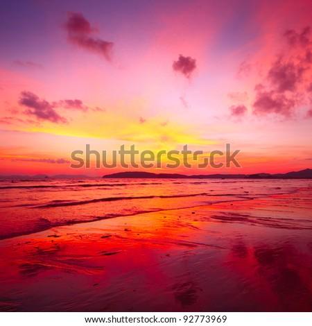 Bright tropical sunset over sea coast - stock photo