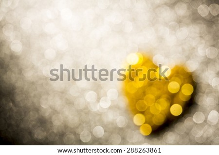 Bright unfocused gold heart shape for abstract bokeh background with copy space - stock photo