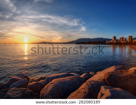 Bright view of the harbor at sunset as a boat docks - stock photo