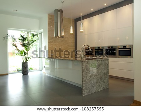 Bright well designed kitchen with travertine wall - stock photo