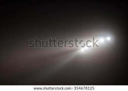 Bright white and yellow Stadium lights with fog  - stock photo