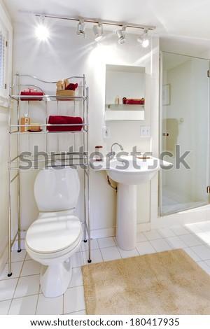 Bright white bathroom with metal mobile shelf storage unit - stock photo