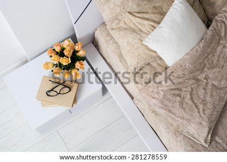 Bright white bedroom interior, cozy bed with beige linen, flowers on a bedside table, shot from above. - stock photo