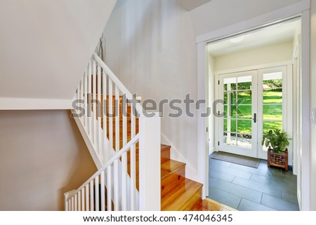 Bright white hallway interior with wooden staircase and door exit to the back yard. Northwest, USA