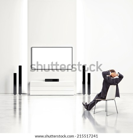 Bright white interior with businessman watching TV - stock photo