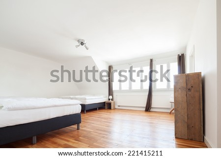 Bright white loft bedroom interior with a row of small windows and two double beds on a wooden parquet floor - stock photo