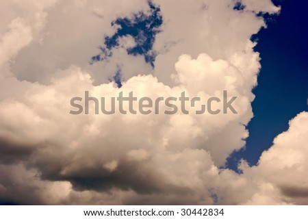 bright white multi level cumulous clouds forming a pocket against a deep blue sky - stock photo