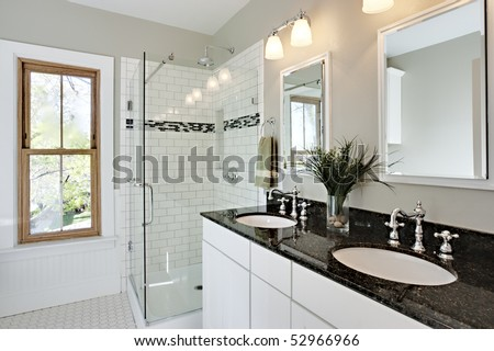 Bright white remodel bathroom. Glass shower and granite counters. - stock photo