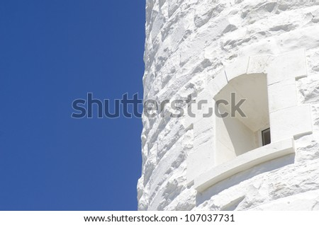 Bright white stone wall of a lighthouse with small window in contrast to clear blue sky as background and copy space. - stock photo