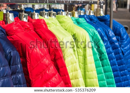 Bright winter clothes hanging at a fashion store