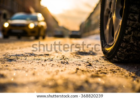 Bright winter sun in a big city, on the snowy street car rides. View from the road level near the wheel - stock photo