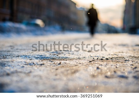 Bright winter sun in a big city, silhouette of the outgoing person on the street. View from the sidewalk level - stock photo