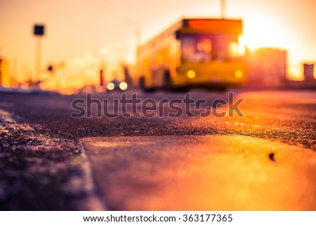 Bright winter sun in a big city, the headlights of approaching bus. View from the level of asphalt, image in the orange-blue toning - stock photo