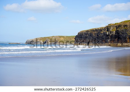 bright winter view of kayaker at ballybunion beach and cliffs on the wild atlantic way in ireland - stock photo