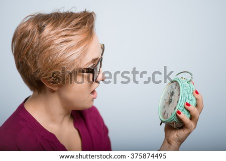 bright woman frightened looks at the alarm clock, with glasses studio isolated - stock photo