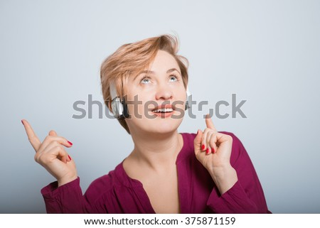 bright woman listening to music on bluetooth headphones, studio isolated