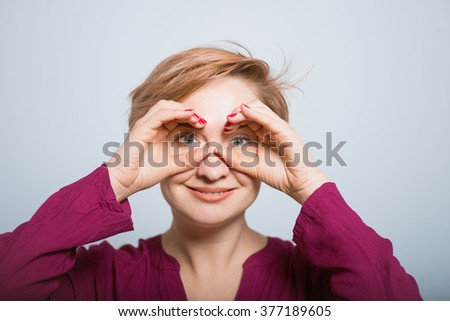 bright woman looking into the distance with a hand-held binoculars, isolated studio - stock photo