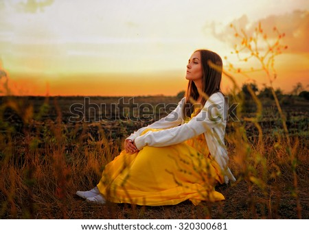 Bright woman relax sitting on a sunset autumn field. - stock photo