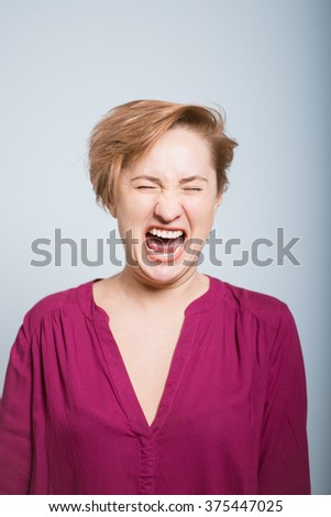 bright woman very funny laughs, on gray background - stock photo