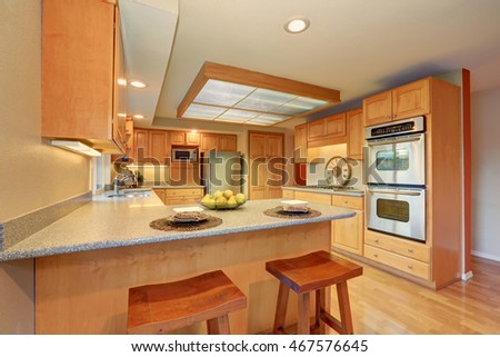 Bright wooden kitchen interior with skylight and steel appliances. Northwest, USA