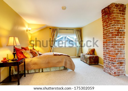 Bright yellow and beige bedroom with carpet floor, brick colomn, cozy beige and olive bedding with red pillows - stock photo