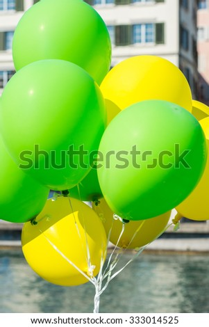 Bright yellow and green balloons on a city street event in summer - stock photo