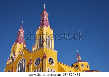 Bright yellow and purple painted facade of the historic Iglesia San Francisco in Castro, capital of the island of Chiloé in Chile - stock photo