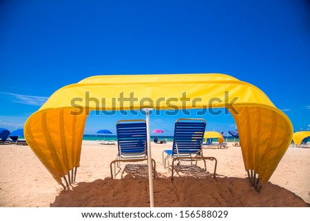Bright yellow beach cabana and chair on the sand - stock photo