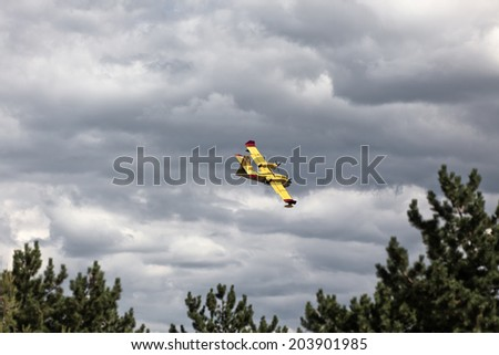 Bright Yellow Firefighter Plane in a Cloudy Sky. Horizontal shot