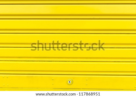 Bright yellow metal sliding door with key hole, taken on a cloudy day.