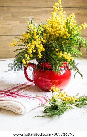 Bright yellow mimosa flowers in a vase on old rustic wooden table - stock photo