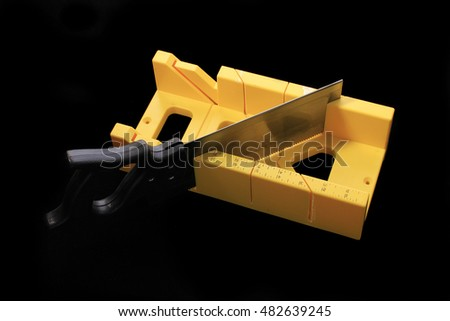Bright yellow mitre box and saw on black background.