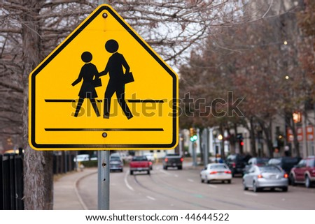 Bright yellow pedestrian crosswalk sign on a busy street with traffic warning motorists to slow down for children crossing the street. - stock photo