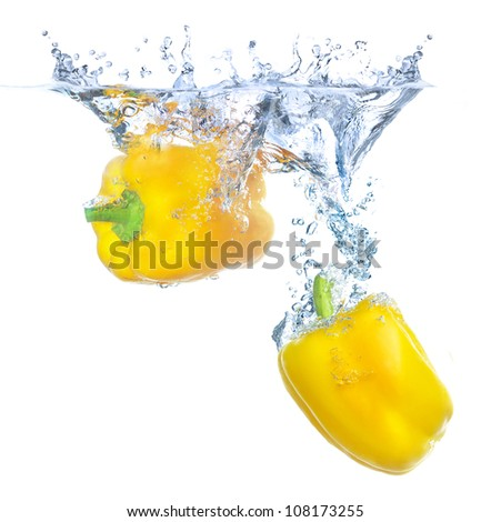 Bright yellow peppers under water. Tasty and healthy food - stock photo