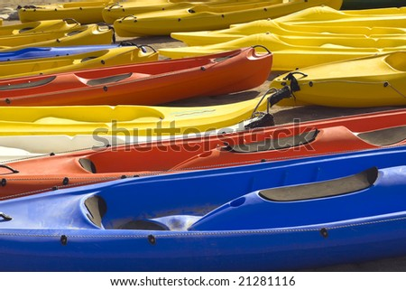 Bright yellow, red and blue canoes lie in two rows on sandy beach