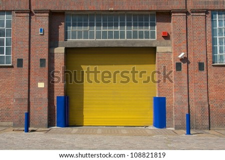 Bright yellow roller shutter at a factory building in London - stock photo