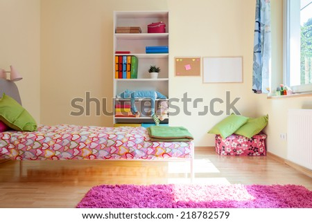 Bright yellow room with pink decorations for girl - stock photo