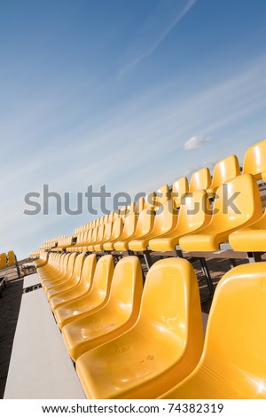 Bright yellow seat rows in a beach tennis court. - stock photo