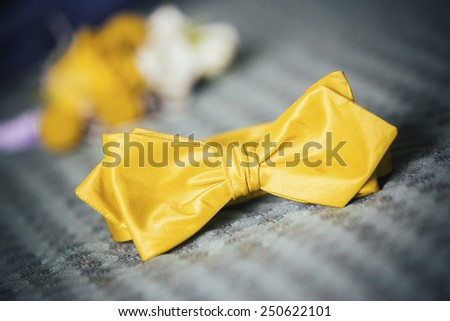 Bright yellow, silk male necktie - a butterfly neatly lying on the bed - stock photo