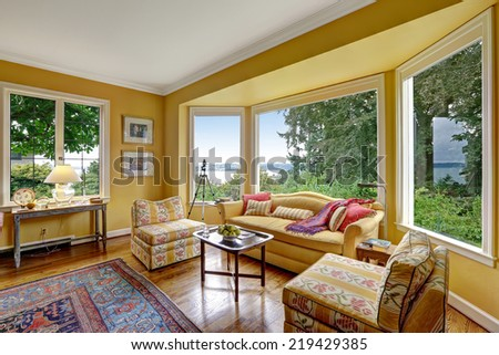 Bright yellow sitting area with wide window and yellow sofa and chairs - stock photo