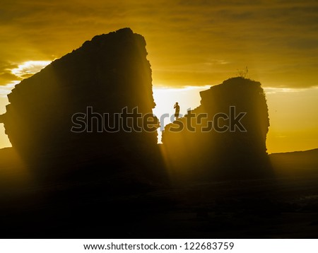 Bright yellow sun on the sea stacks with silhouette of a person standing on the top of a rock