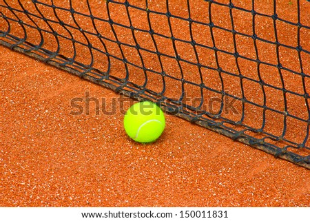 Bright yellow tennis ball on the court