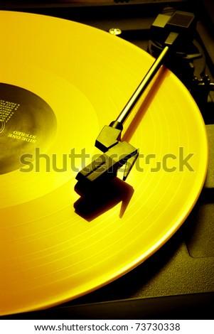 Bright yellow vinyl record shot on phonograph - stock photo