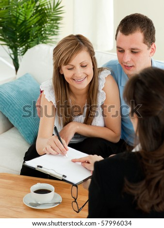 Bright young couple signing a contract sitting in their living room with a saleswoman - stock photo