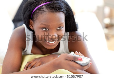 Bright young woman watching TV lying on a sofa in the living-room - stock photo