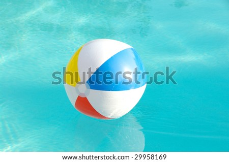 Brightly colored beach ball floating in a swimming pool
