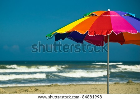 Brightly colored beach umbrella with waves and blue sky in the background - stock photo