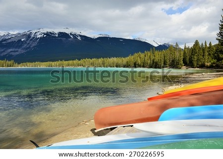Brightly Colored Canoes on the Shore of Crystal Clear Lake - stock photo