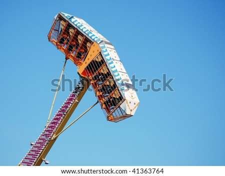 Brightly colored carnival ride swinging high in the sky on a cloudless, sunny day. The ride is an enclosed basket that holds several people on the end of a swinging arm, thrilling upside down riders.